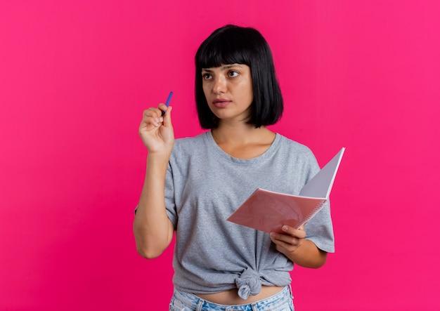 Piękna młoda brunetka kaukaski dziewczyna trzyma pióro i notatnik patrząc z boku