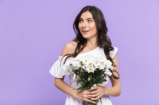 Piękna młoda brunetka kobieta stojąca na białym tle nad fioletową ścianą, trzymając stokrotki