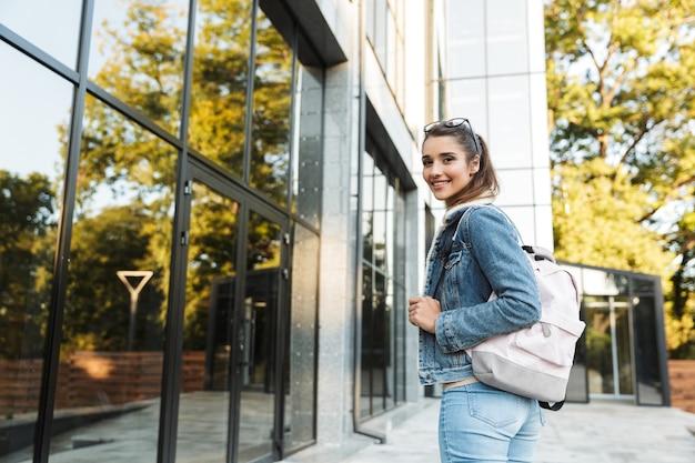 Piękna młoda brunetka kobieta ubrana w kurtkę, niosąc plecak chodzenie na zewnątrz