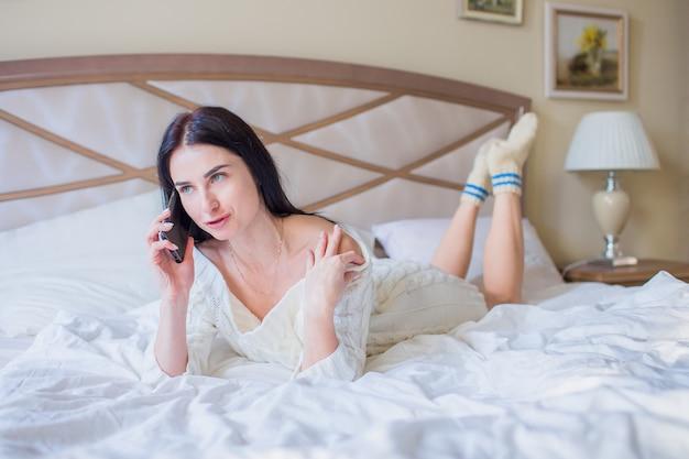 Piękna młoda brunetka kobieta w białej sukni z dzianiny rozmawia przez telefon, leżąc w łóżku w domu lub w hotelu i śmiejąc się