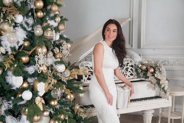 Piękna młoda brunetka kobieta w białej wieczorowej sukni koktajlowej z białym fortepianem i udekorowaną choinką z prezentami w klasycznym luksusowym wnętrzu.