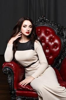 Piękna młoda brunetka kobieta w długiej sukni koloru kremu z kręconymi włosami, doskonały makijaż i manicure.