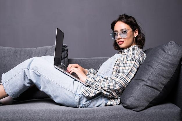 Piękna młoda brunetka kobieta w domu siedzi na kanapie lub kanapa przy użyciu swojego komputera przenośnego i uśmiechnięty