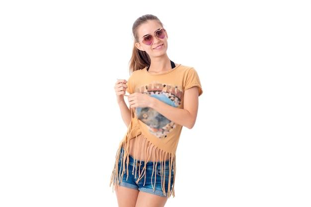 Piękna młoda brunetka kobieta w okularach przeciwsłonecznych i letnie ubrania na białym tle na białej ścianie