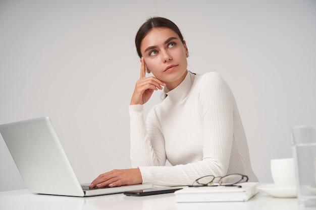 Piękna młoda brunetka kobieta z fryzurą kucyka pracuje z laptopem w biurze, trzymając głowę z podniesioną ręką i patrząc w zadumie na bok, odizolowana na białej ścianie