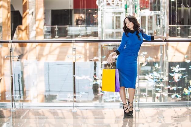 Piękna młoda brunetka w niebieskiej sukience z żółtym opakowaniem w ręku w centrum handlowym sklepu