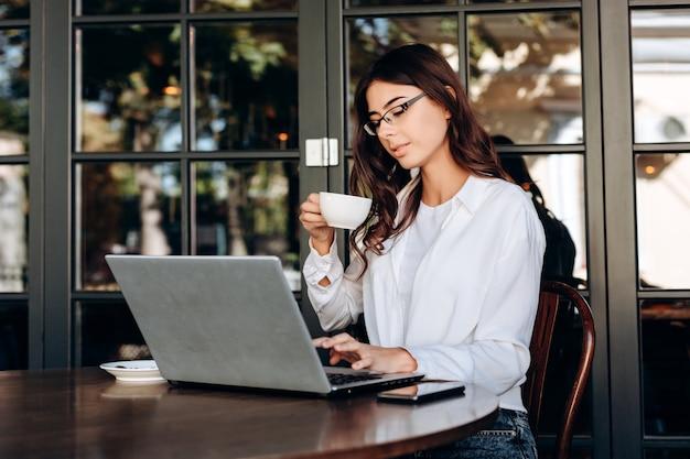Piękna, młoda brunetka w okularach pije kawę i pracuje na komputerze
