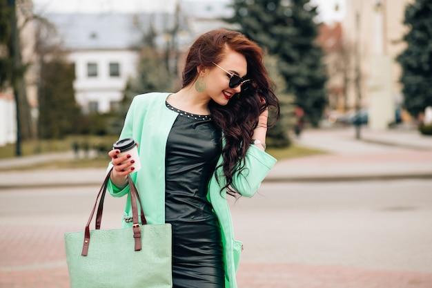 Piękna młoda brunetka z długimi falującymi włosami, cienkimi, smukłymi sylwetkami, idealnym ciałem i ładnym makijażem twarzy, ubrana w czerwoną wieczorową obcisłą sukienkę i biżuterię. letnie akcesoria, kolekcja sukienek projektowych