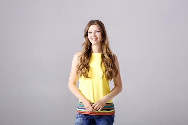 Piękna młoda brunetka z długimi włosami, uśmiechnięta i patrząca w kamerę