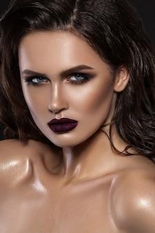 Piękna młoda brunetka z makijażem i długimi włosami
