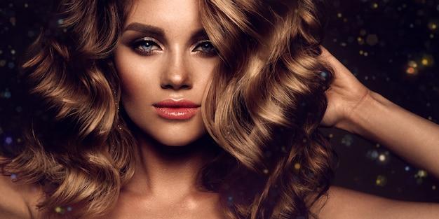 Piękna młoda brunetka z makijażem i kręconymi włosami