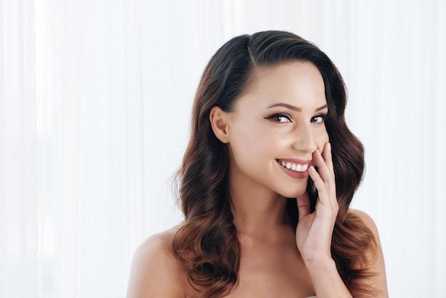 Piękna młoda brunetka z nagimi ramionami, dotykając policzka i uśmiechając się