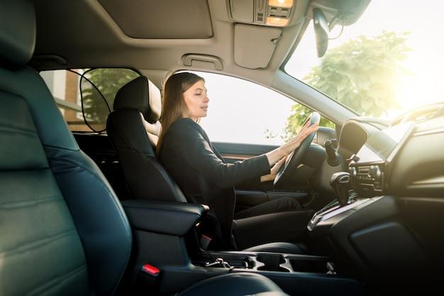 Piękna młoda brunetki kobieta jedzie samochód biuro w garniturze. bizneswoman jedzie samochód w mieście. widok z boku, słoneczny dzień