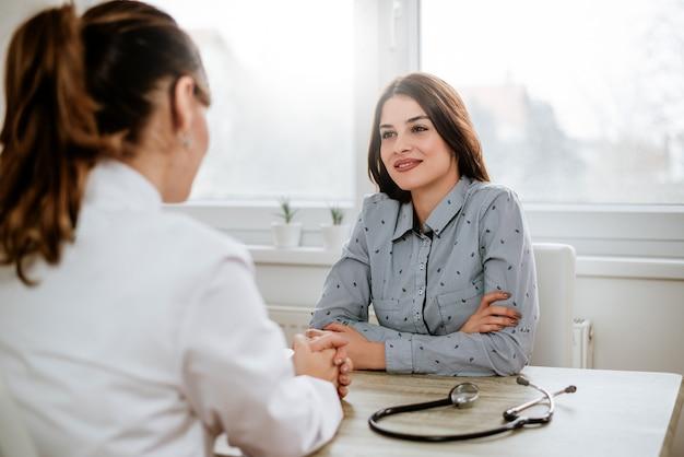 Piękna młoda brunetki kobieta przy lekarki biurem.