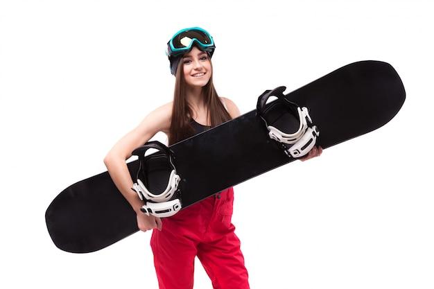 Piękna młoda brunetki kobieta w czerń krótkim podkoszulku bez rękawów chwyta snowboard