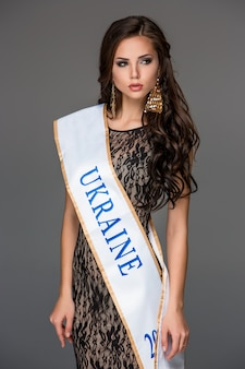Piękna młoda brunetki kobieta z jej włosy pozuje w ai długiej sukni.