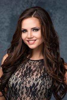 Piękna młoda brunetki kobieta z jej włosy pozuje w maswerk sukni.