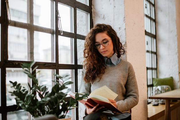 Piękna młoda brunetki kobiety czytelnicza książka blisko okno w domu.