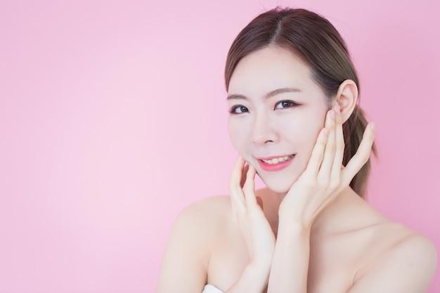 Piękna młoda caucasian azjatykcia kobieta dotyka jej czystą świeżą skóry twarz. kosmetologia, pielęgnacja skóry, czyszczenie twarzy