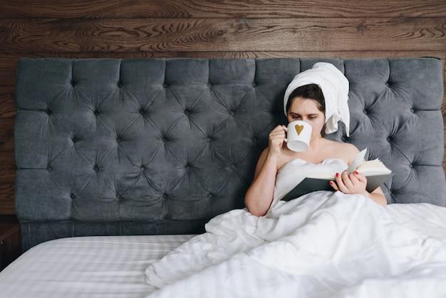 Piękna młoda caucasian kobieta czyta książkę w łóżku i pije filiżankę kawy