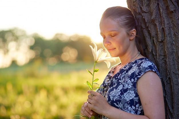 Piękna młoda caucasian kobieta stoi w lesie na letnim dniu przy zmierzchem z leluja kwiatem