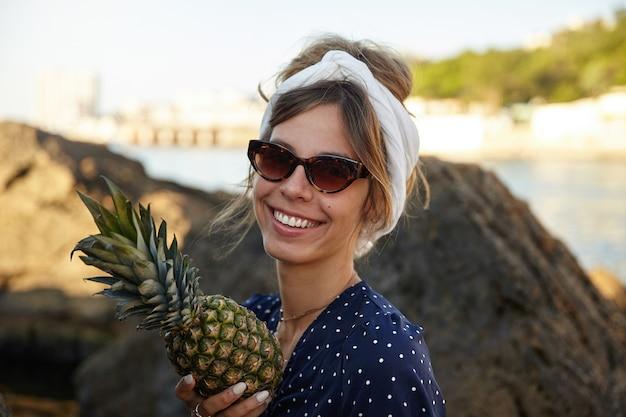 Piękna młoda ciemnowłosa kobieta z przypadkową fryzurą, nosząca opaskę i patrząc z szerokim, szczęśliwym uśmiechem, pozująca nad zatoką morską w słoneczny letni dzień ze świeżym ananasem w dłoni