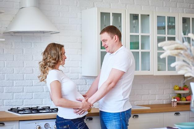 Piękna młoda ciężarna dziewczyna z mężem śmia się w kuchni w pięknym wnętrzu.