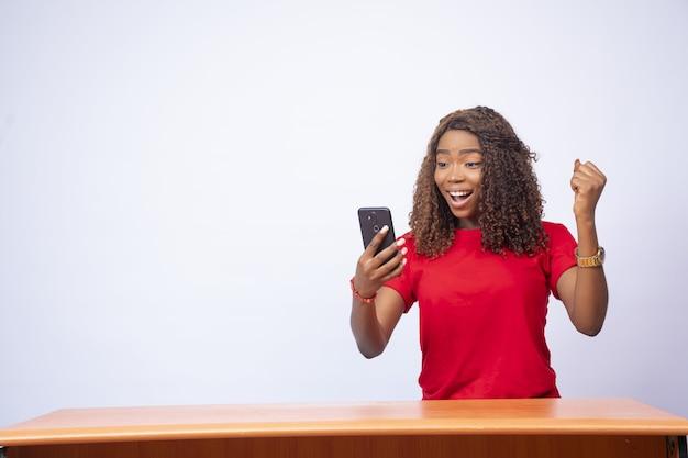 Piękna młoda czarna kobieta siedzi przy biurku, patrząc na swój telefon i czując podekscytowanie
