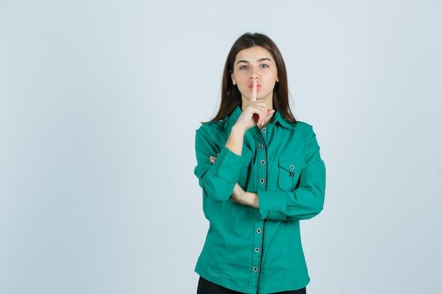 Piękna młoda dama pokazując gest ciszy w zielonej koszuli i patrząc ostrożnie. przedni widok.