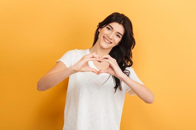 Piękna młoda dama pokazuje gest miłości serca.
