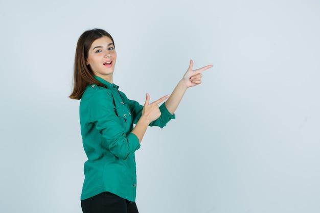 Piękna młoda dama pokazuje gest pistoletu w zielonej koszuli i wygląda pewnie. .