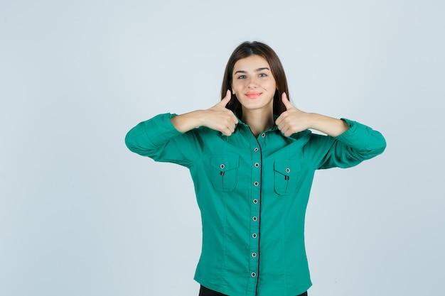 Piękna młoda dama pokazuje podwójne kciuki w zielonej koszuli i wygląda wesoło. przedni widok.