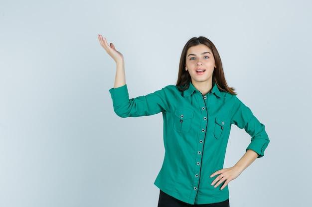 Piękna młoda dama pokazuje powitalny gest w zielonej koszuli i patrzy wesoło, widok z przodu.