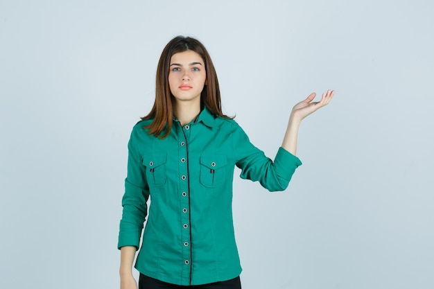 Piękna młoda dama robi gest powitalny w zielonej koszuli i wygląda zdziwiona, widok z przodu.