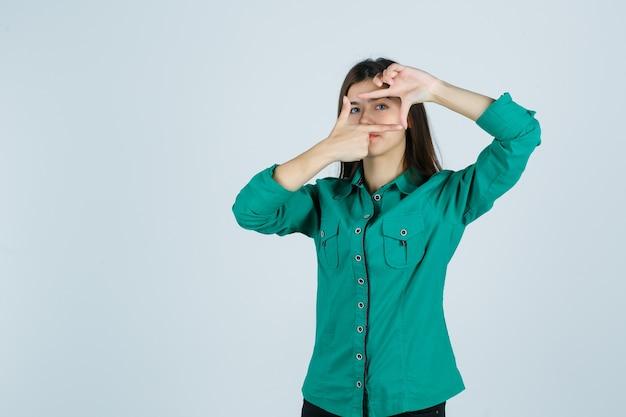 Piękna młoda dama robi gest ramy w zielonej koszuli i wygląda pewnie. przedni widok.
