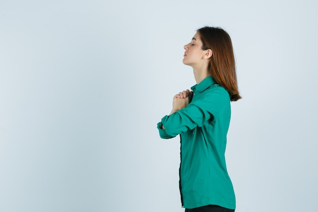 Piękna młoda dama, ściskając ręce w geście modlitwy w zielonej koszuli i patrząc z nadzieją.