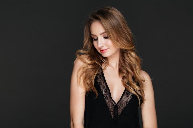 Piękna młoda dama stoi i pozuje nad szarości ścianą