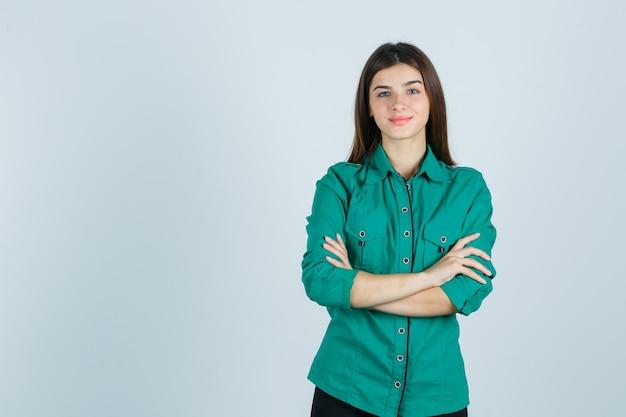 Piękna młoda dama trzyma ręce złożone w zielonej koszuli i wygląda pozytywnie. przedni widok.