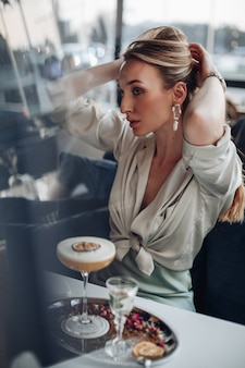 Piękna młoda dama trzymająca blond włosy i robiąca kucyk przed śniadaniem w kawiarni