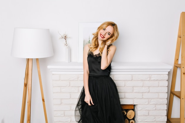 Piękna młoda dama ubrana w elegancką czarną sukienkę w białym pokoju, pozowanie, uśmiechając się. dotyka swoich długich pięknych, falowanych złotych włosów.