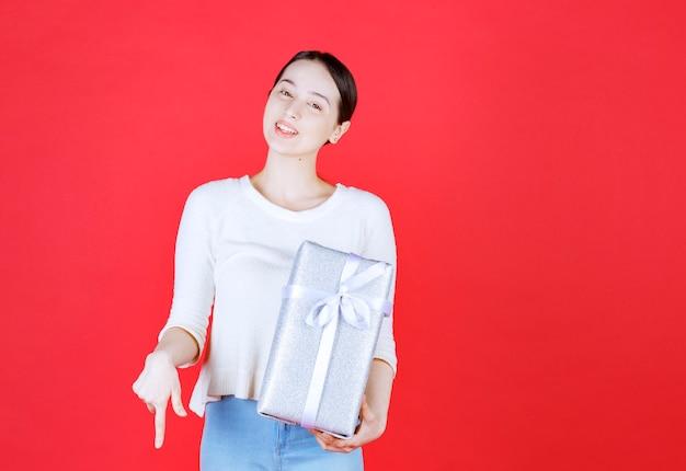 Piękna młoda dama uśmiecha się i trzyma zapakowane pudełko na prezent