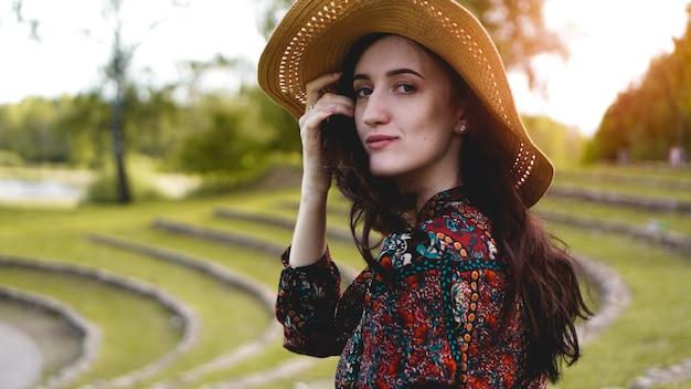 Piękna młoda dama w blasku przez sukienkę dotyk słomkowego kapelusza. dziewczyna spaceruje po zboczu wzgórza jak uprawa ryżu