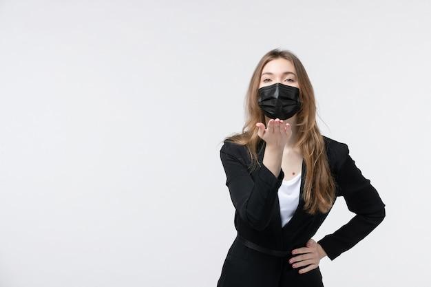 Piękna młoda dama w garniturze nosząca maskę chirurgiczną i wysyłająca gest pocałunku na białym