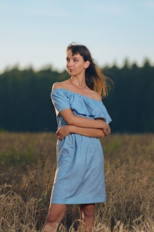 Piękna młoda dama w pszenicznym polu przy zmierzchem