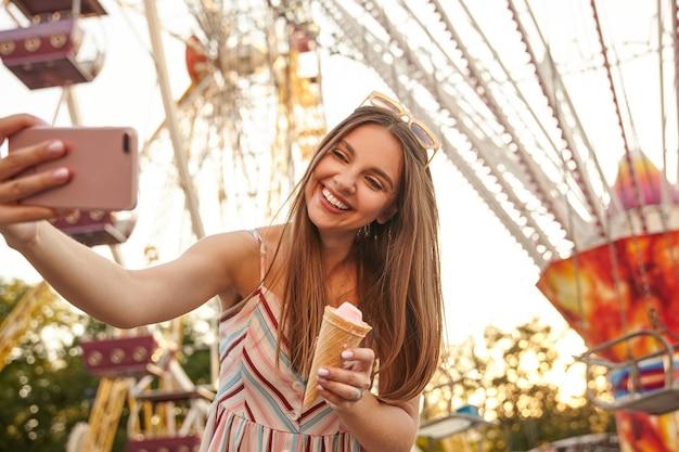Piękna młoda długowłosa brunetka dama w romantycznej letniej sukience pozuje nad atrakcjami podczas robienia selfie z telefonem komórkowym, trzymając w dłoni lody w dłoni i uśmiechając się radośnie