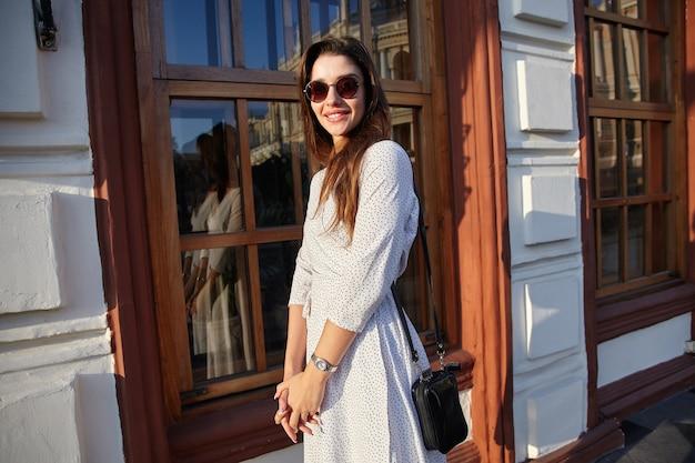 Piękna młoda długowłosa brunetka kobieta w okularach przeciwsłonecznych patrząc z czarującym uśmiechem spacerując ulicą w ciepły jasny dzień, spotykając się z przyjaciółmi w weekend