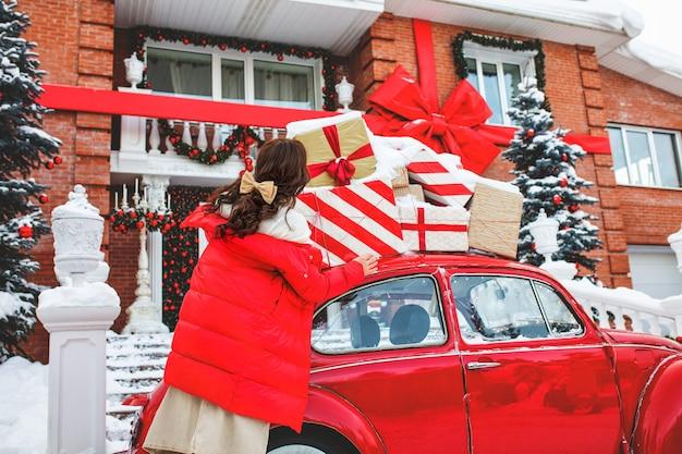 Piękna młoda dorosła dziewczyna, wesoła i szczęśliwa przy czerwonym samochodzie na tle domu w ozdoby świąteczne
