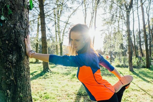 Piękna młoda dorosła kobieta rozciągająca mięśnie czworogłowe przed bieganiem w zalesionym parku o zachodzie słońca punkt koncepcji sport higieny osobistej bieganie