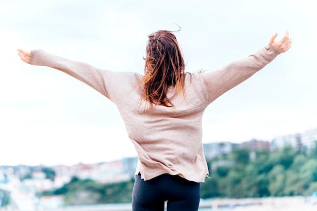 Piękna młoda dorosła kobieta z otwartymi ramionami uśmiechająca się z poczuciem wolności