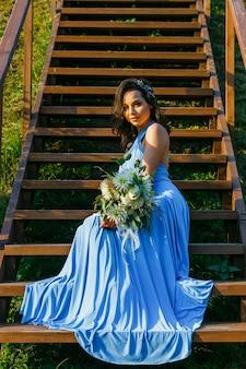 Piękna młoda druhna z kręconymi włosami pozuje na ceremonii ślubnej